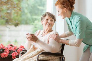 A professional caretaker in uniform helping a geriatric female p
